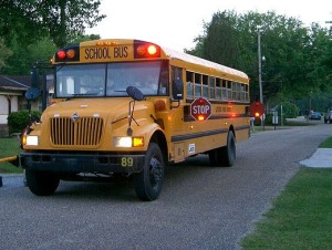 A school bus with its flashers on about 1/2 mile down the road